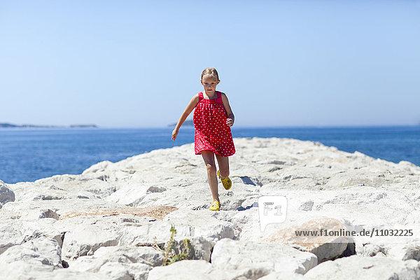 Girl running on stone pier