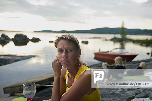 Woman sitting at lake  children in background  Siljan  Dalarna  Sweden
