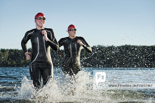 Woman in wetsuit running in sea  Sweden