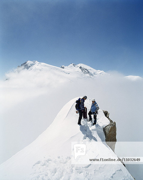 Two Mountain Climbers on a Snowy Mountain Top.