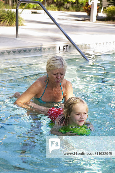 Grandmother and granddaughter in swimming pool