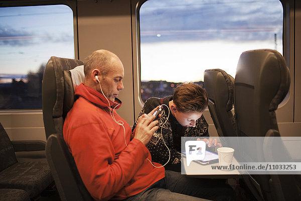 Man and teenage boy using tablet on train