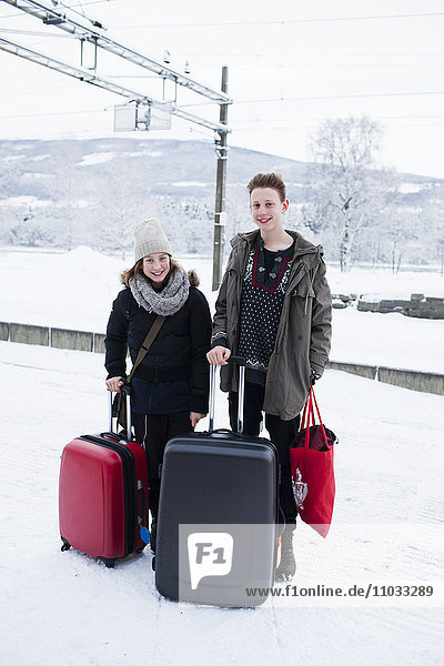 Teenagers with suitcases on train platform