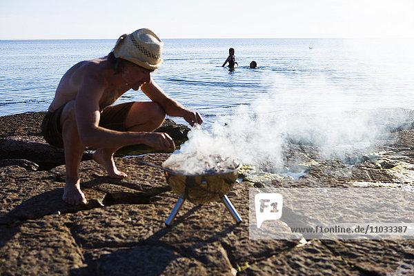 A man with an outdoor grill on the beach.