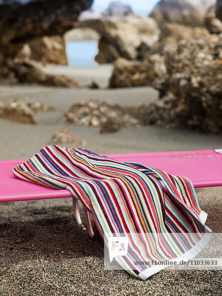 Sunlounger with towel on rocky beach
