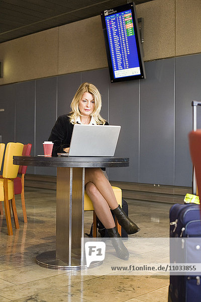 A business woman with laptop on airport.