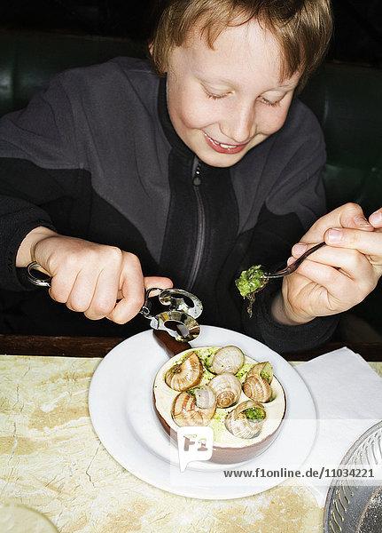 A boy eating snails.
