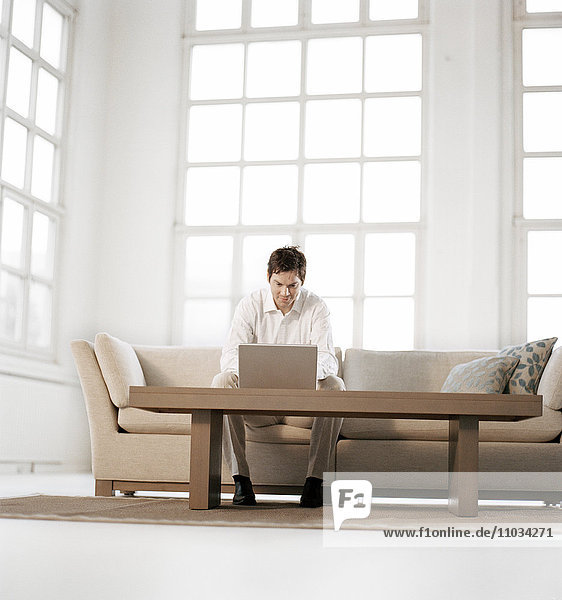 A man working on a laptop in a living room.