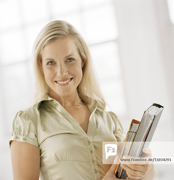 Portrait of woman holding files.