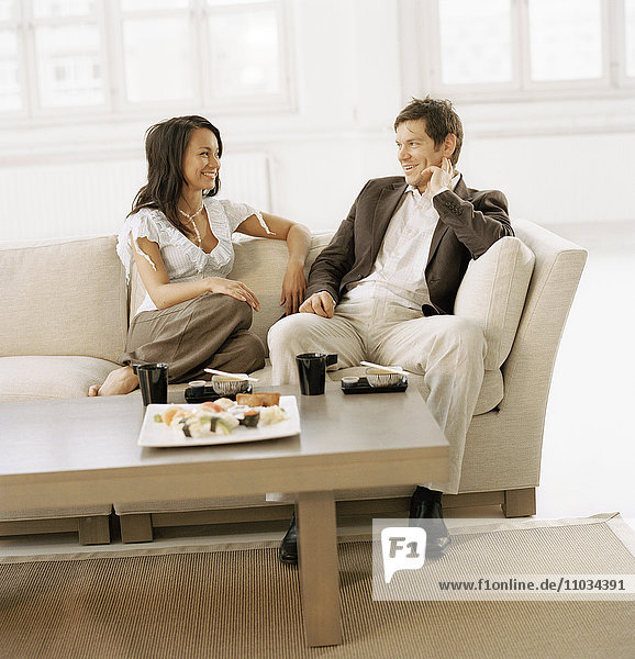 A couple sitting in the living room eating sushi.
