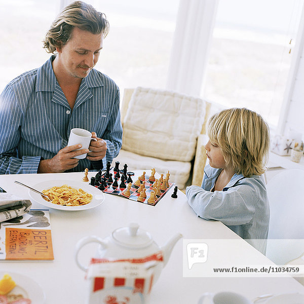 Father and son playing chess at the breakfast table  Sweden.