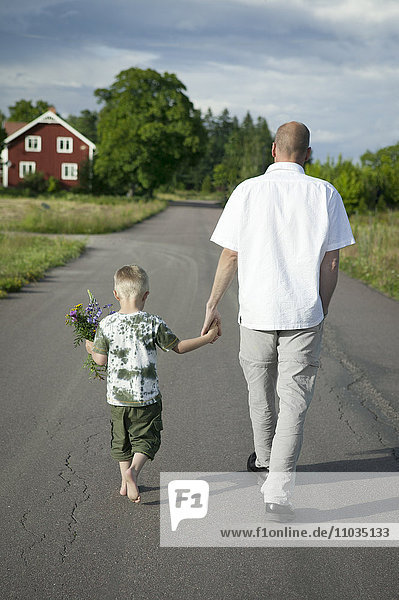 Father walking with son on road  boy holding flowers