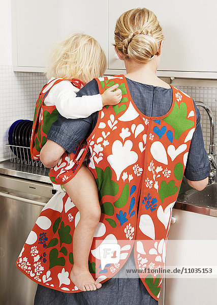 Mother with son in kitchen  rear view