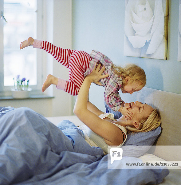 Mother and daughter playing in a bed.