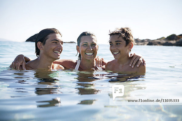 Mother with sons bathing in sea