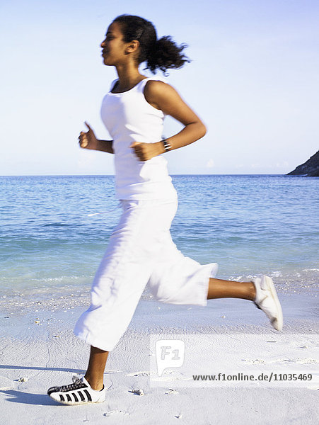 A woman jogging on a beach.