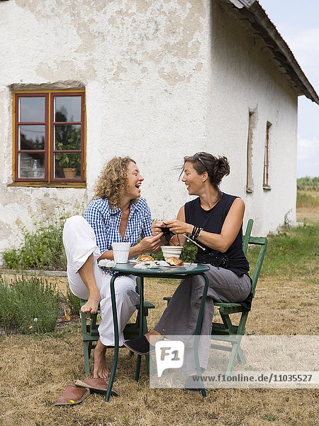 Women sitting outdoors in front of a house.