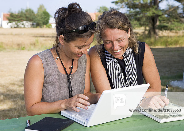 Two women working together on a laptop.