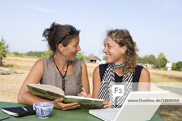Two women with a book and a laptop.
