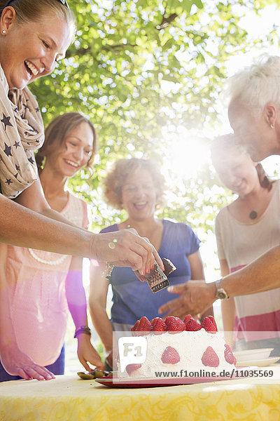 Women preparing strawberry cake in garden