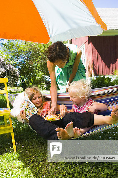 Two girls getting snacks from their mother in a hammock.