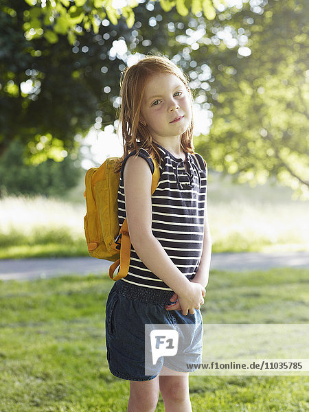 Girl with backpack standing in park