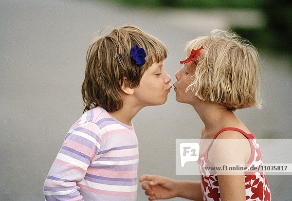 A girl and boy kissing.