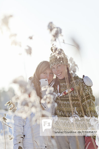 Teenage girl with mother looking through frosted grass