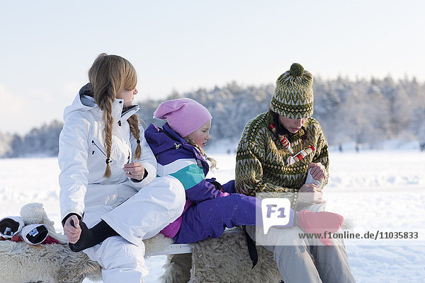 Mother with two daughters sitting on bench