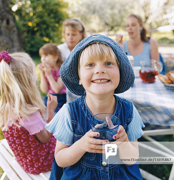 A smiling girl with sun cap drinking lemonade together with other children and adults.