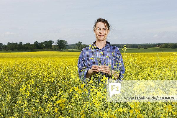 Smiling woman on oilseed rape field