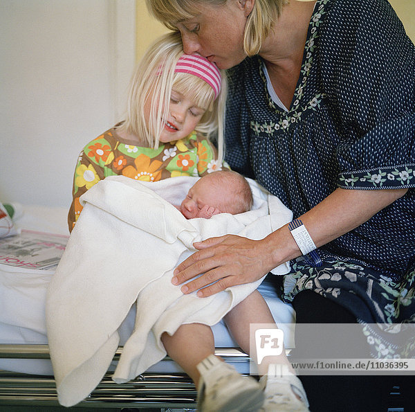 A girl with her newborn baby brother and mother  Sweden.