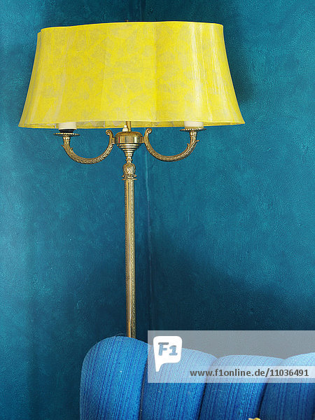A yellow lamp in a blue room.