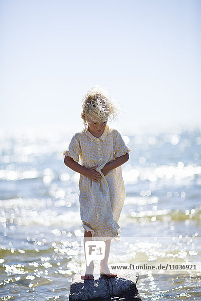 Girl on a rock in a sparkling sea  Sweden.