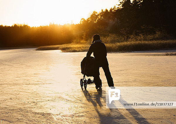 Father skating with a baby carriage  Sweden.
