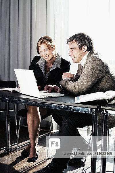 Two businesspeople having by a laptop  Sweden.