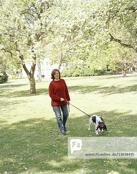 Woman goes for a walk with dog.