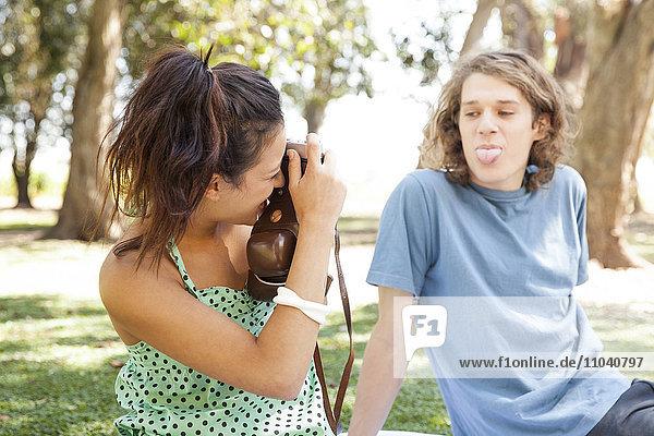 Frau fotografiert Freundin im Park