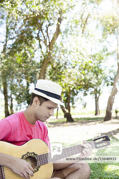 Mann spielt Akustikgitarre