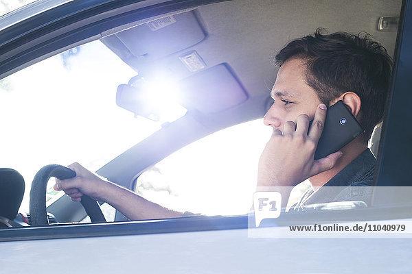 Fahrer mit Handy ohne Freisprecheinrichtung während der Fahrt