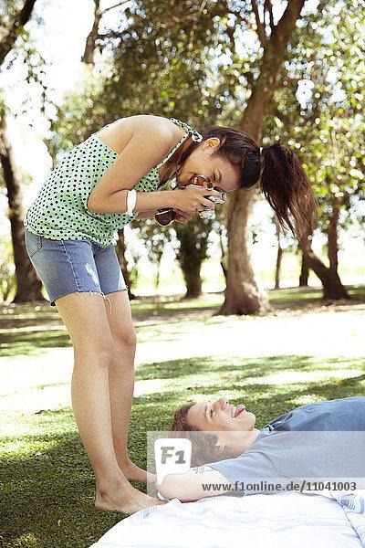Junge Frau fotografiert Freund im Park