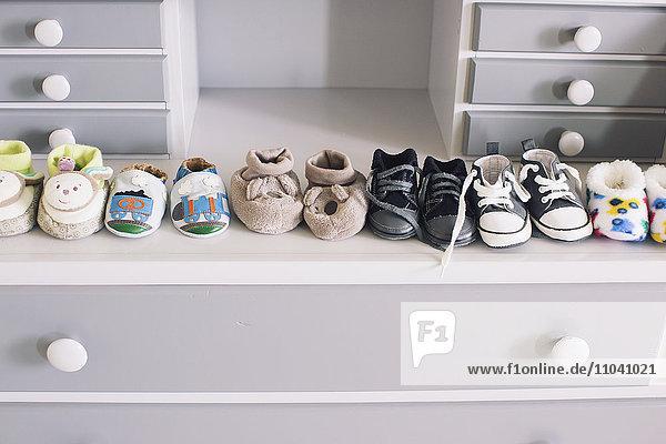 Reihe von Babyschuhen auf der Kommode