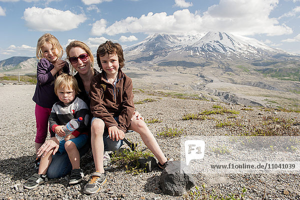 Mother and children posing in front of Mount St. Helens  Washington  USA