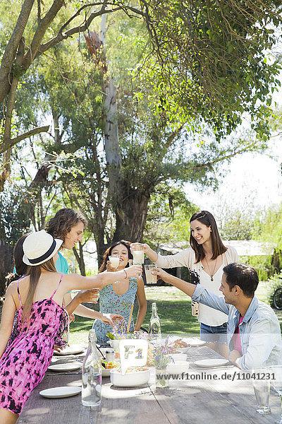 Freunde beim gemeinsamen Essen im Freien  Gläser klirren