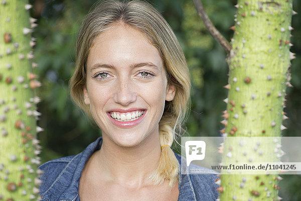 Junge Frau lächelt fröhlich im Freien  Portrait