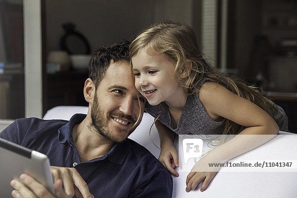 Vater und Tochter verwenden gemeinsam ein digitales Tablett