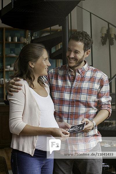 Ein Paar  das sich gemeinsam ein Ultraschallbild ansieht.