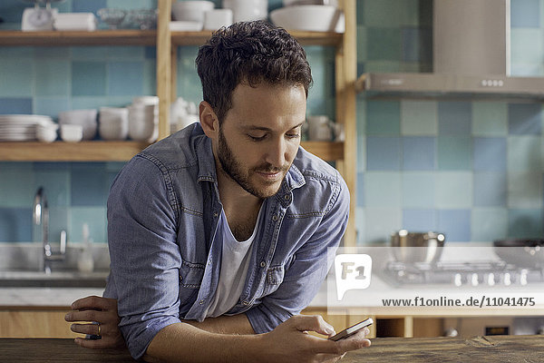 Mann zu Hause in der Küche Text-Messaging