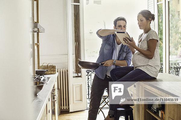 Paare  die während der Zubereitung einer Mahlzeit auf ein digitales Tablett referenzieren