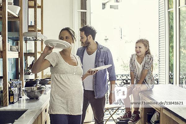 Mädchen bei der Zubereitung des Familienessens durch die Eltern